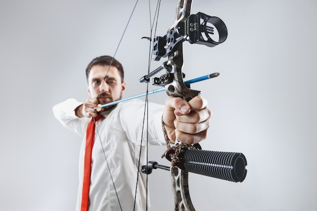 灰色のスタジオの壁に分離された弓矢でターゲットを狙うビジネスマン