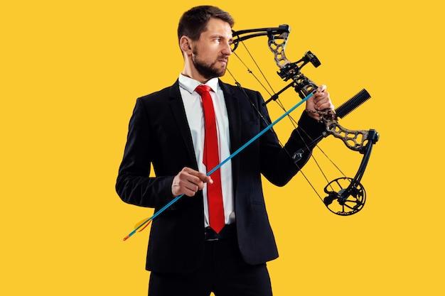 黄色のスタジオの背景に分離された弓と矢でターゲットを狙うビジネスマン。ビジネス、目標、挑戦、競争、達成の概念 無料写真