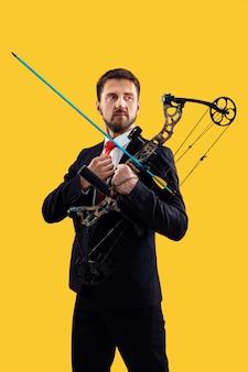 黄色のスタジオの背景に分離された弓と矢でターゲットを狙うビジネスマン。ビジネス、目標、挑戦、競争、達成の概念
