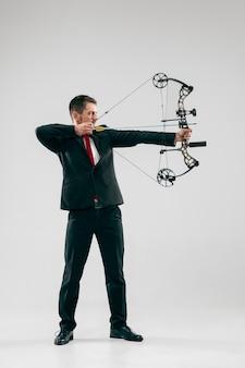 Uomo d'affari che mira al bersaglio con arco e frecce, isolato su sfondo grigio.