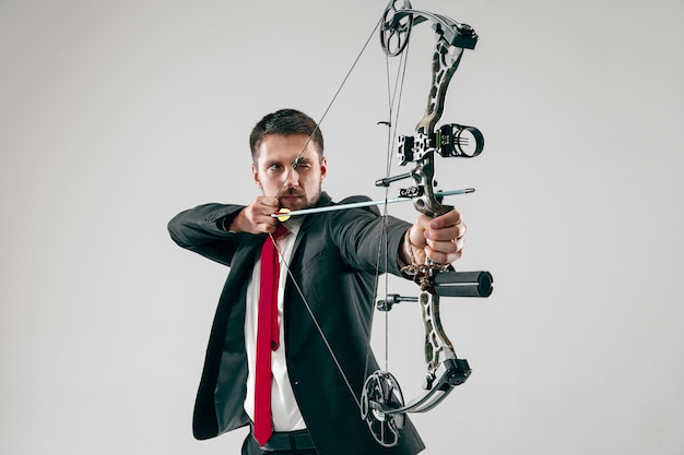 Businessman aiming at target with bow and arrow isolated on gray  background.