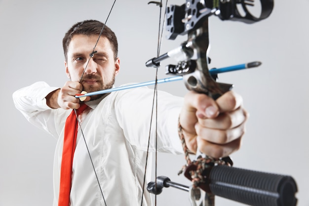 Businessman aiming at target with bow and arrow, isolated on gray background.