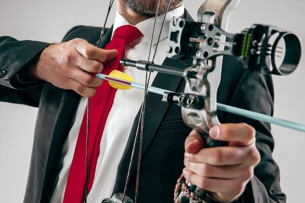Uomo d'affari che mira al bersaglio con arco e freccia isolato su sfondo grigio studio. il concetto di business, obiettivo, sfida, concorrenza, realizzazione, scopo, vittoria, vittoria, chiarezza, vincitore e successo