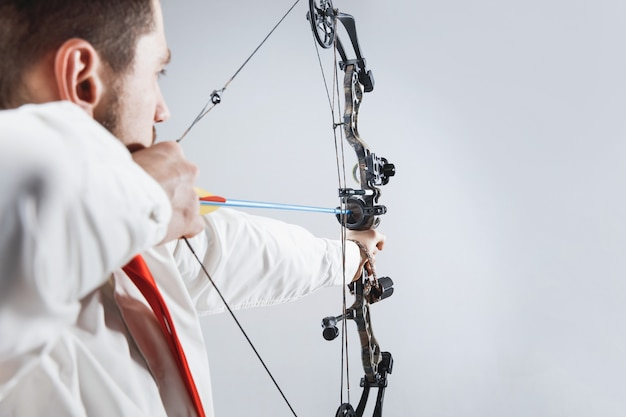 Businessman aiming at target with bow and arrow, isolated on gray studio background.