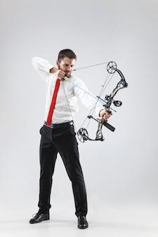 Uomo d'affari che mira al bersaglio con arco e frecce, isolato su sfondo grigio studio.