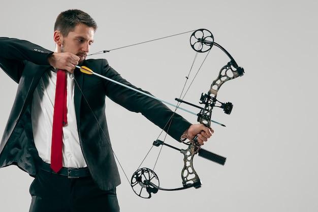 Uomo d'affari che mira al bersaglio con arco e freccia, isolato sulla parete grigia dello studio