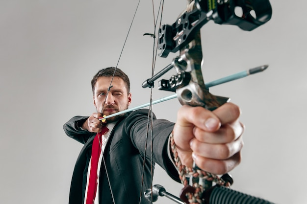 Uomo d'affari che mira al bersaglio con arco e frecce, isolato su sfondo bianco