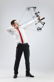 Businessman aiming at target with bow and arrow, isolated on white background