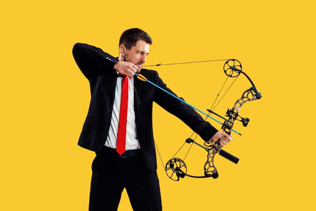 Businessman aiming at target with bow and arrow, isolated on yellow background