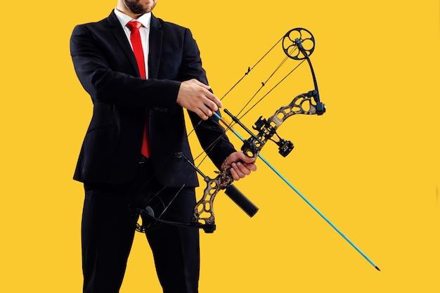 Uomo d'affari che mira al bersaglio con arco e frecce, isolato su sfondo giallo studio. il business, l'obiettivo, la sfida, la concorrenza, il concetto di realizzazione
