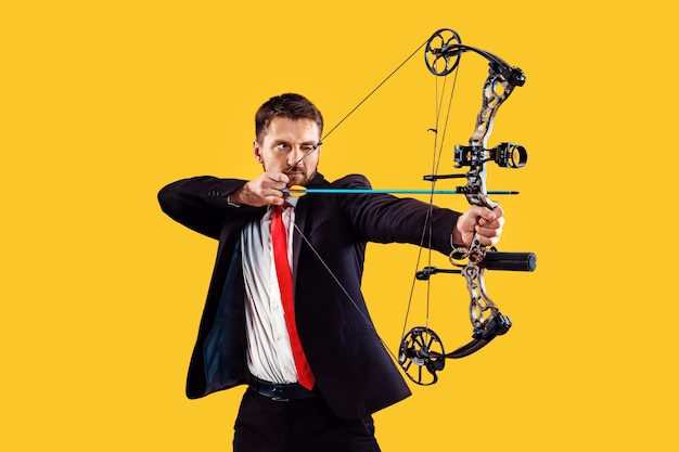 Businessman aiming at target with bow and arrow, isolated on yellow studio wall