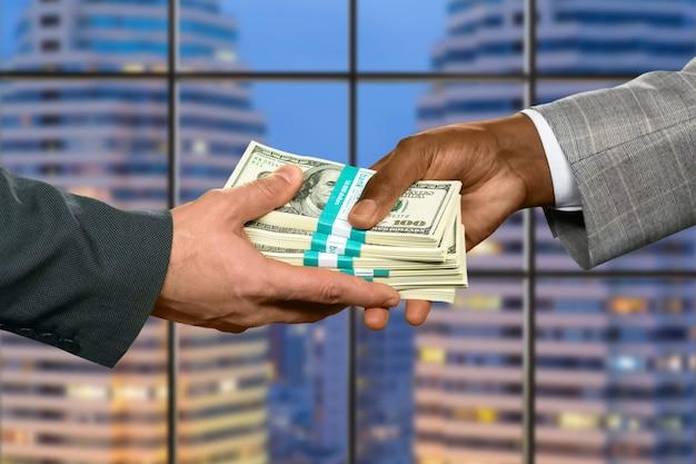 大きなお金を取っているビジネスマンの手。市内の債務を返済します。彼はかなりの割合を獲得しました。セールスマンにとって良い月です。