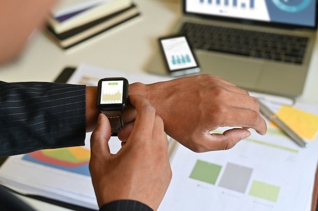 Businessman analysis data in smart watch on office desk.