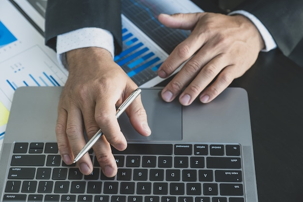 Businessman analysis the finance graph with laptop at the office for setting challenging management business goals and planning to achieve the new target