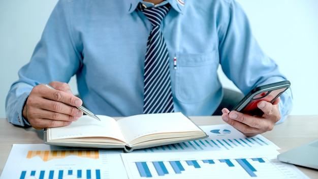 사업가는 도전적인 비즈니스 목표를 설정하기 위해 사무실에서 노트북으로 차트를 분석