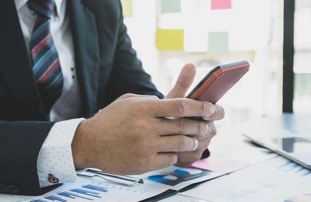 Бизнесмен анализирует финансовый график с помощью смартфона в офисе для постановки сложных бизнес-целей управления и планирования для достижения новой цели.