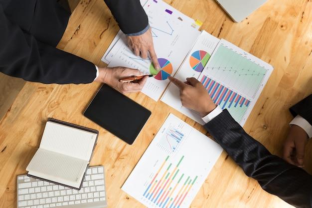 ビジネスマンの分析とタブレットと書類のドキュメントとの議論