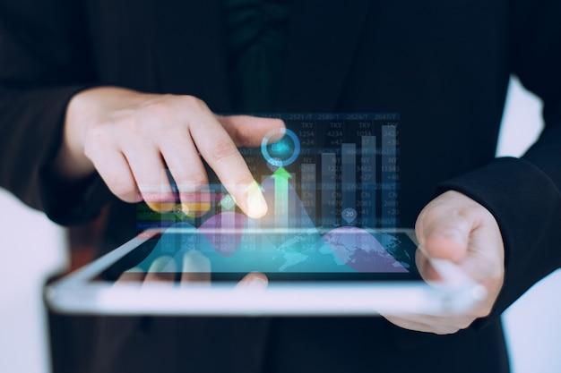 ビジネスマンは、デジタル拡張グラフィックスを使用して会社の財務バランスを分析します。ビジネスおよびマーケティング技術の概念。