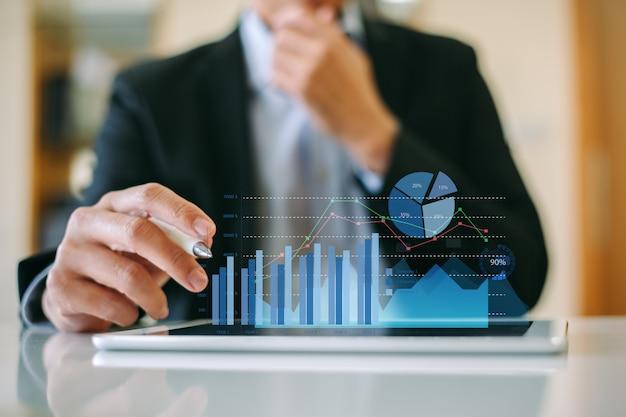 Бизнесмен анализируя финансовую компании путем работы с цифровыми графиками дополненной реальности.