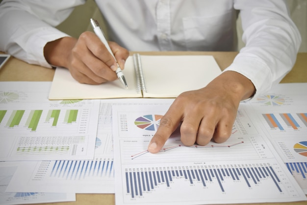 Businessman analyzing financial graphs and charts on desk