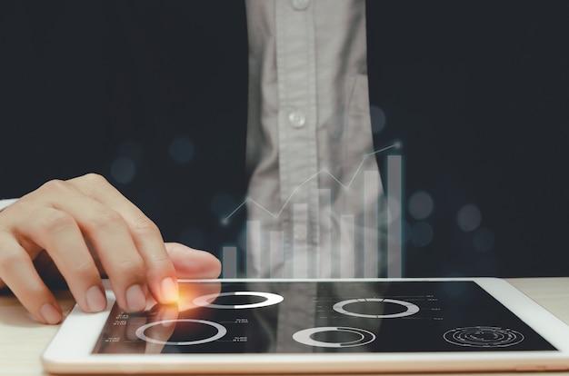 Бизнесмен, анализируя графики и диаграммы, сообщает статистику прибыли и роста в планшетах.
