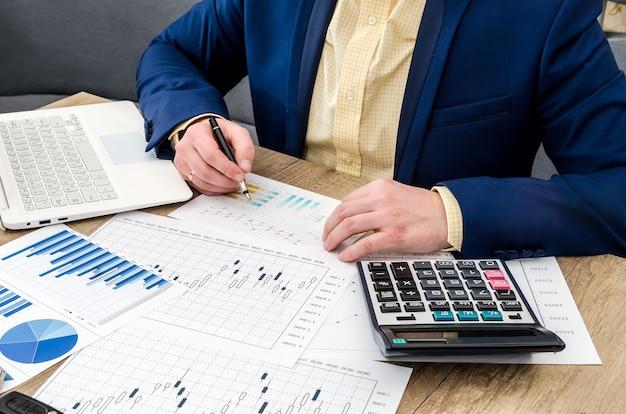 木製のテーブルのグラフや図を分析するビジネスマン
