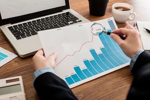 ビジネスマンは、オフィスで成長チャートを分析します。