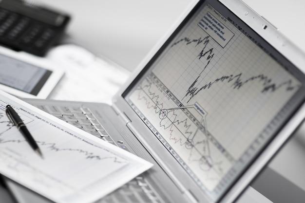 ノートパソコンで投資チャートを分析するビジネスマン。
