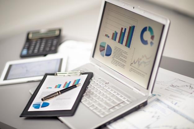 Бизнесмен, анализируя графики инвестиций с ноутбуком. бухгалтерия