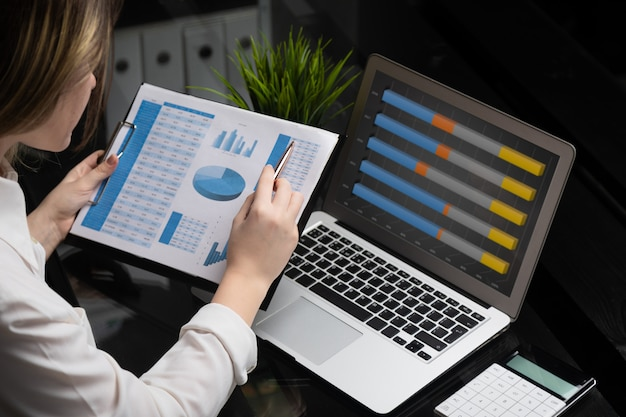 ビジネスマンのラップトップで投資チャートを分析します。経理