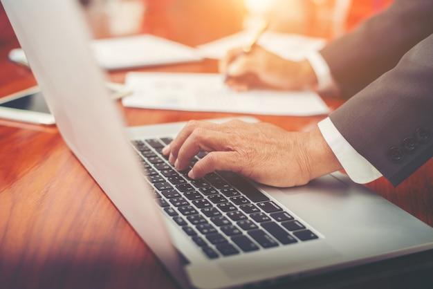 Imprenditore analizzando i grafici di investimento con il computer portatile in ufficio.