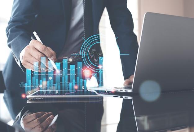 금융 그래프가 있는 디지털 태블릿 및 노트북에 대한 시장 보고서를 분석하는 사업가