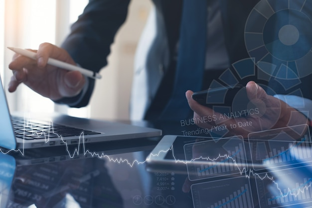 Businessman analyzing marketing data with analytics diagram on virtual screen