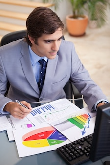 그의 책상에서 통계를 분석하는 사업