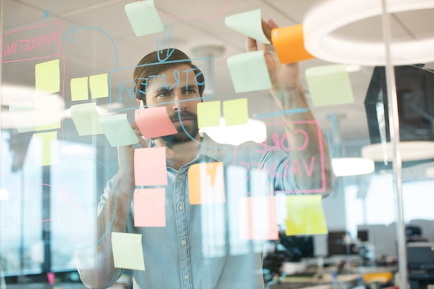 Бизнесмен, анализирующий страсти на стекле при использовании мобильного телефона