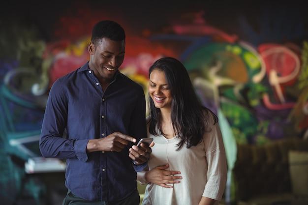 Бизнесмен и коллега обсуждают по мобильному телефону