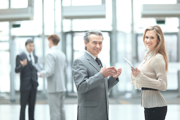 사업가와 조수가 흐릿한 사무실 배경에서 작업 문제에 대해 논의합니다.