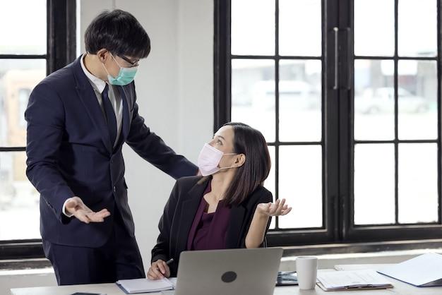 Covid-19 때문에 얼굴 마스크와 coworking 사무실에서 책상에 앉아 사업가 및 아름다운 사업가