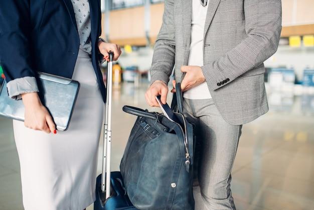 空港で出発を待っているビジネスマンやビジネスの女性