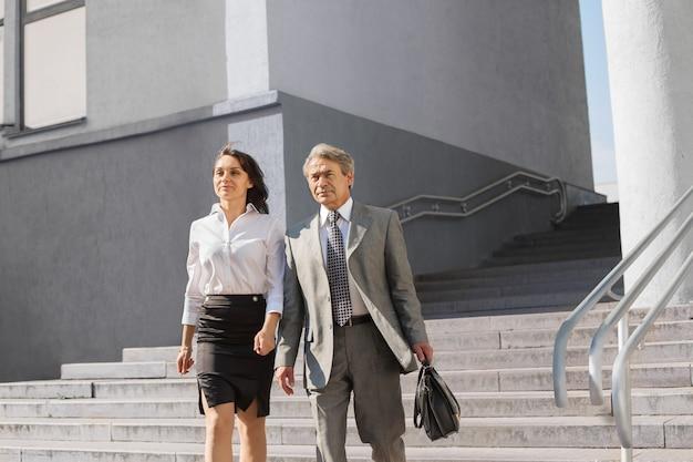 ビジネスマンとビジネスウーマンがオフィスから出てきます