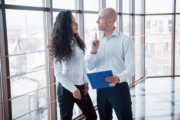 Бизнесмен и деловая женщина изучают диаграмму на табличке и бумажные документы у окна на фоне городского управления на высоком этаже