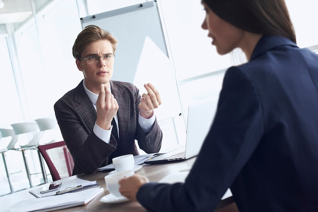 Бизнесмен и бизнес-леди в офисе, работая вместе, сидя за столом, пить горячий кофе, обсуждая проект, сконцентрированный женщина крупным планом