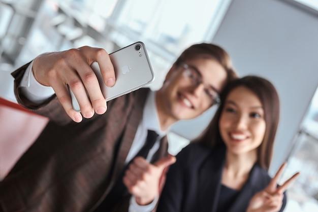 사무실에서 함께 일하는 사업가와 사업가는 테이블에 앉아 스마트폰으로 셀카 사진을 찍고 쾌활한 흐릿한 미소를 짓고 있습니다.
