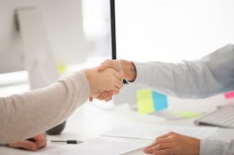 契約または成功した交渉に署名した後のビジネスマンおよびビジネスウーマンハンドシェイク