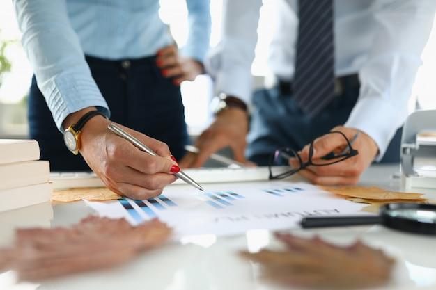 Бизнесмен и коммерсантка в офисе анализируют план осени.