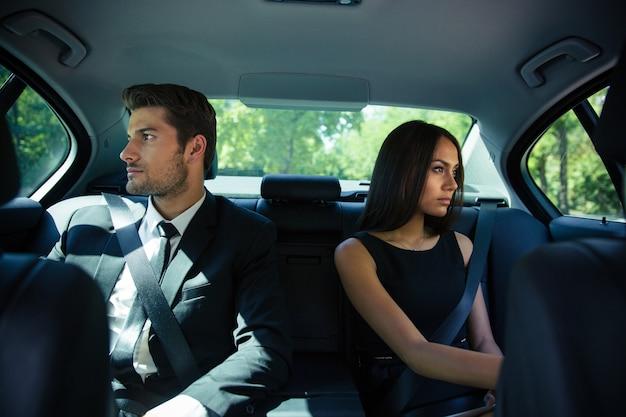 Бизнесмен и бизнесвумен, езда на заднем сиденье в роскошном автомобиле