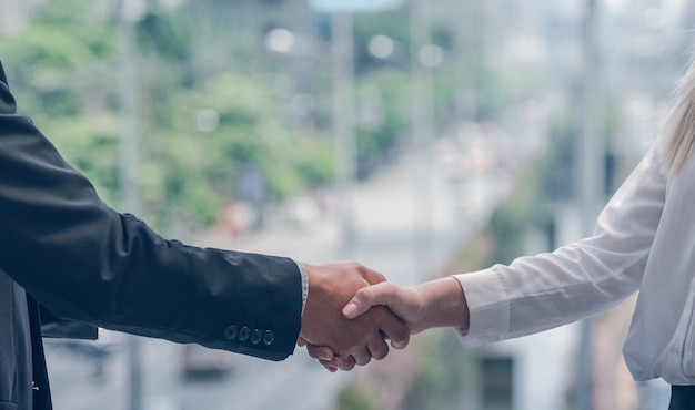 ビジネスマンやビジネスウーマンが合意の概念の成功のために手を振る