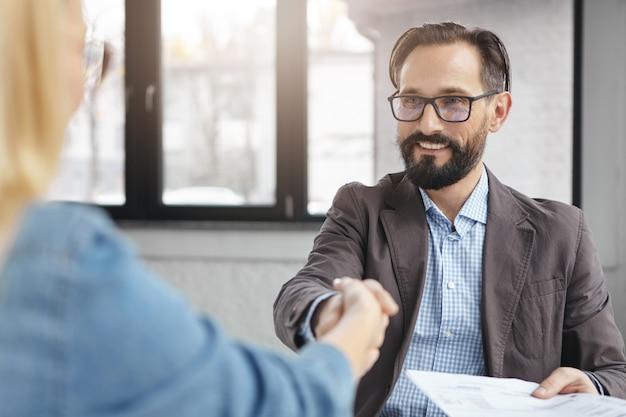 Бизнесмен и бизнесвумен пожимают друг другу руки после успешного подписания контракта