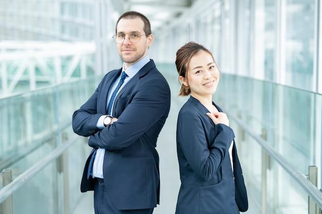 Бизнесмен и бизнесвумен, стоя спиной к спине в здании