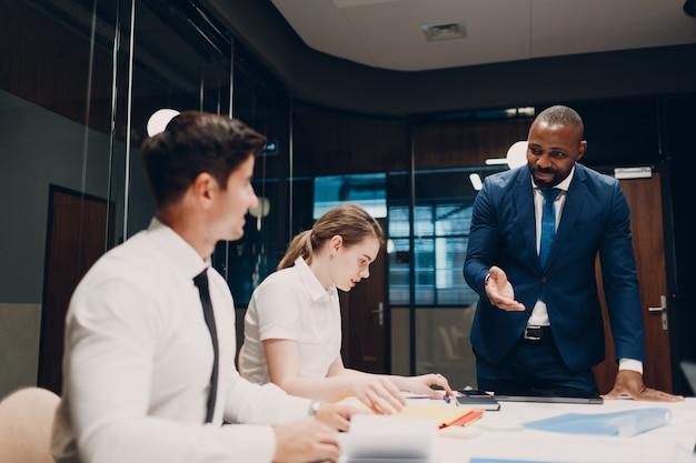 オフィス会議でビジネスマンと実業家のチーム。ビジネスマングループ会議の議論は上司の男性と女性とテーブルに座っています。